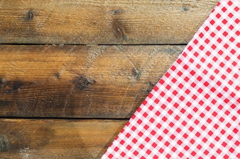 Folded red checkered napkin on wooden table