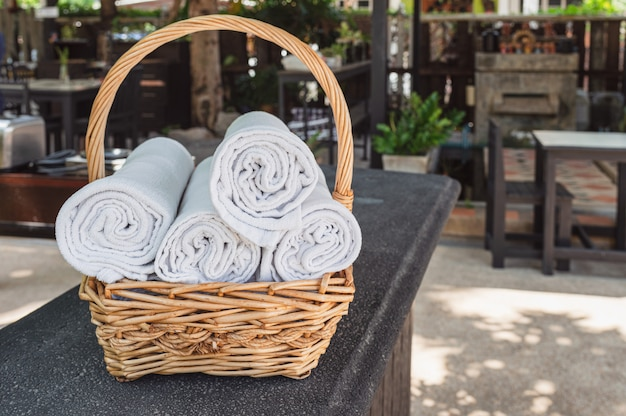 Folded roll towels stacked in wooden basket