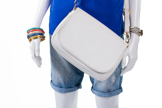 가죽 핸드백이 달린 접힌 반바지. 마네킹에 간단한 흰색 가방입니다. 화려한 보석과 일반 지갑. 저렴한 가죽 핸드백 재고 있습니다.