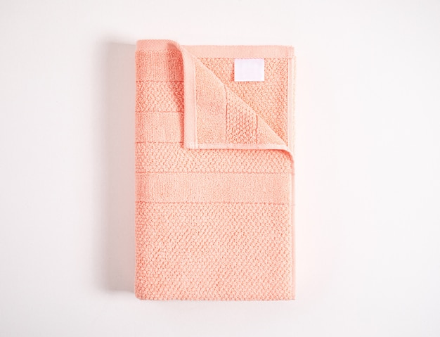 Folded soft coral terry towel with white empty label against white background