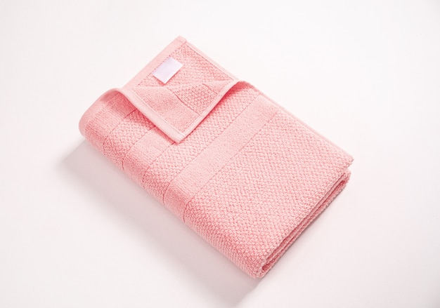 Folded soft pink terry towel with white empty label against white background