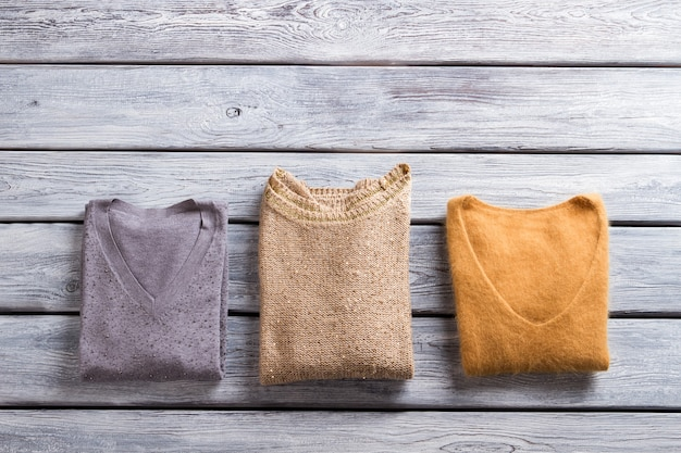 다른 색상의 접힌 스웨터. v넥이 있는 캐주얼 풀오버. 회색 선반에 따뜻한 옷. 소녀들을 위한 고품질 가을 옷.