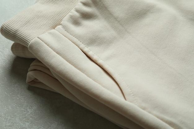 흰색 질감에 접힌 트레이닝 복 바지를 닫습니다.