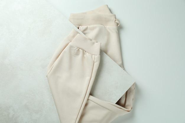 Сложенные спортивные штаны на белой текстурированной поверхности, вид сверху