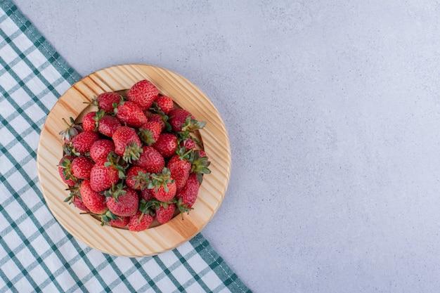 大理石の背景にイチゴの山と大皿の下に折りたたまれたテーブルクロス。高品質の写真