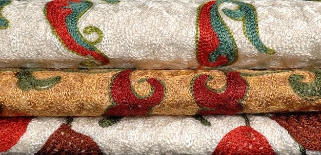 ゴールドカラーで刺繍された折り畳まれた3つのロール東アジアとアジアのテキスタイル