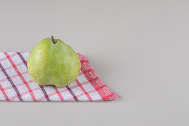 Asciugamano piegato sotto una pera su marmo