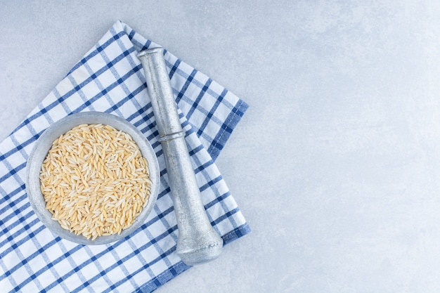 Asciugamano piegato sotto uno schiacciatore di erbe e una brocca di metallo di riso integrale su una superficie di marmo