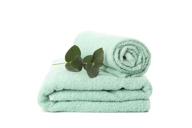 Сложенные полотенца и эвкалипт, изолированные на белом