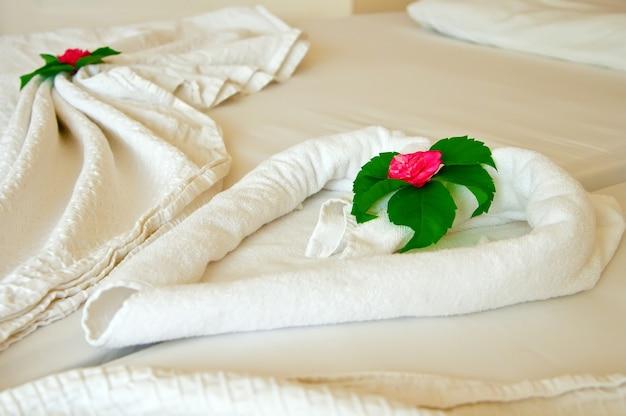 ホテルのベッドで折りたたまれたタオルと花