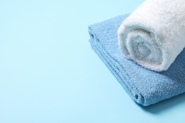 Folded towels on blue, close up and space for text