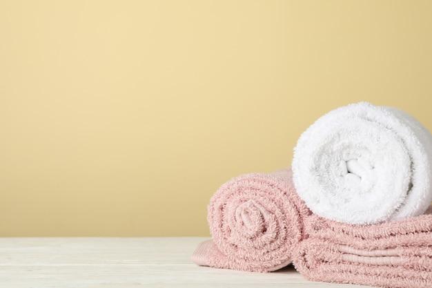Сложенные полотенца на белом деревянном столе на бежевом, место для текста