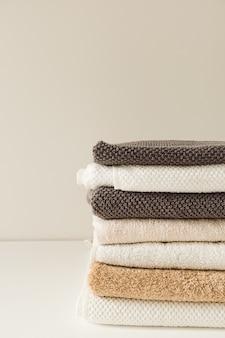 折りたたまれたタオルは白い背景の上に積み重ねます。ヘルスケア、衛生、ウェルネス構成。