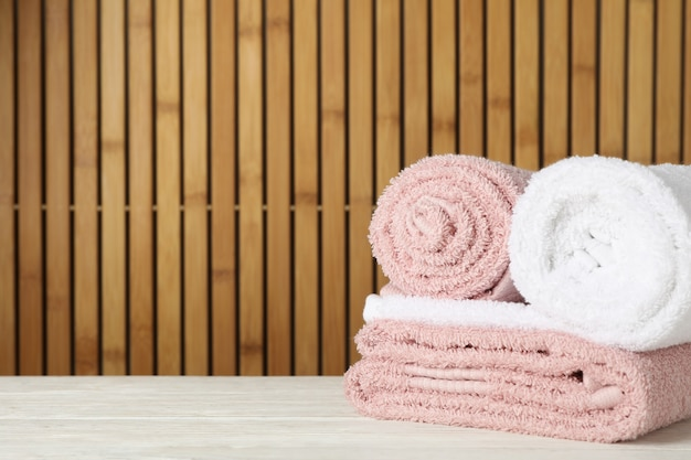 Folded towels on wooden table on bamboo, space for text