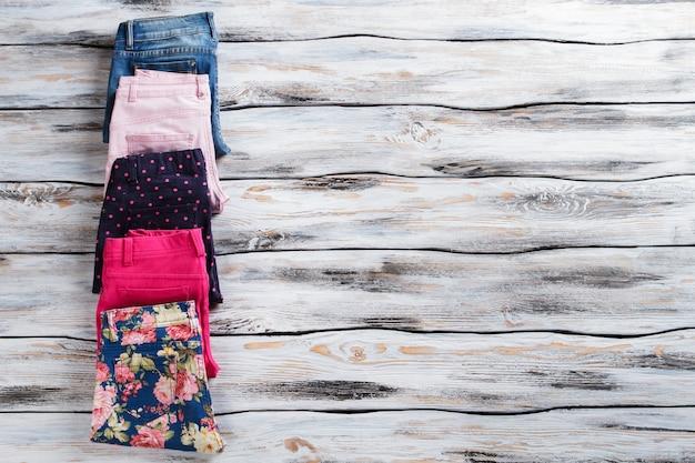 Сложенные брюки и синие джинсы. брюки и брюки из денима для девочек. дизайнерские брюки продаются в бутике. калейдоскоп цветов.