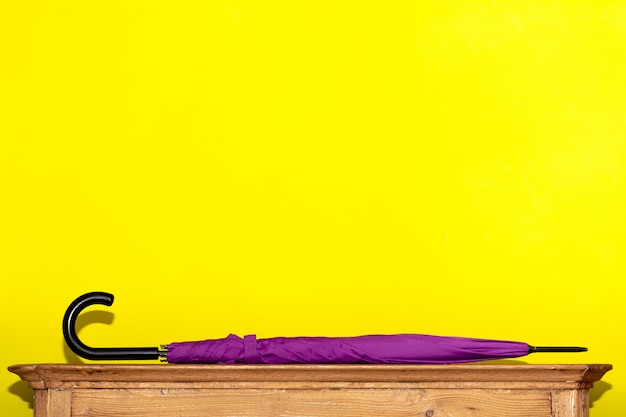 A folded umbrella in purple lies on a wooden chest of drawers against a yellow wall. concept interior, order in the house.
