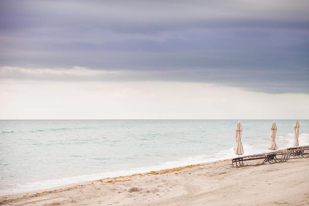Сложенные зонтики на пустом песчаном пляже у океана ранним утром