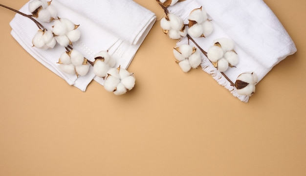Folded white cotton terry towel and sprigs of cotton flower on a light brown background, top view , copy space
