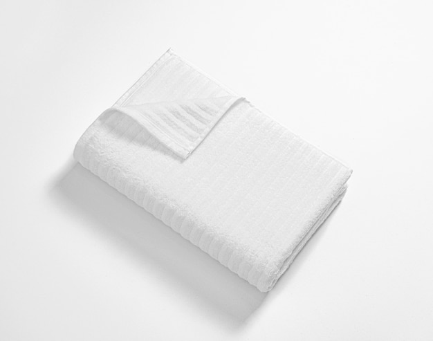Folded white soft terry towel against white background