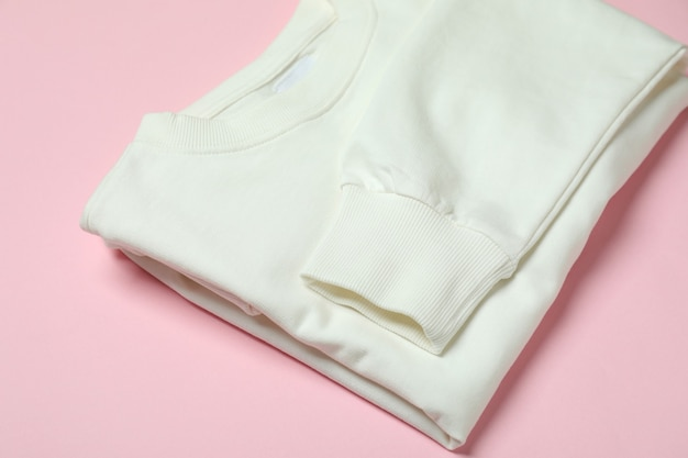 ピンクの背景に白いスウェットシャツを折りたたむ