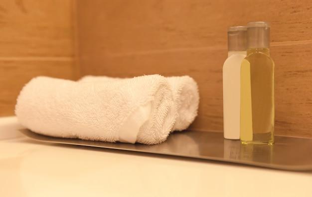 木製の背景をぼかした写真にホテルスパバスルームのテーブルに白いタオルを折り