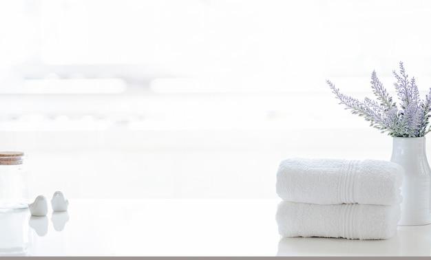 Сложенные белые полотенца на белом столе с копией пространства на размытом фоне