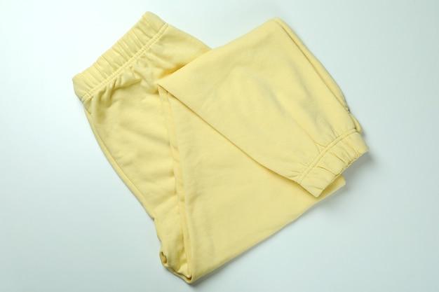 흰색 바탕에 접힌 된 노란색 트레이닝 복 바지