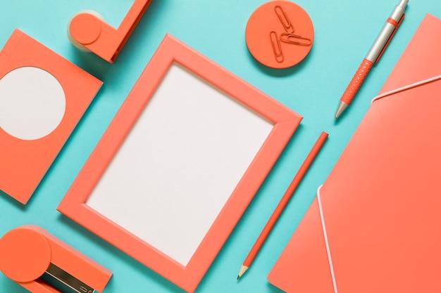 Папка, пустая рамка и открытка возле канцелярских товаров