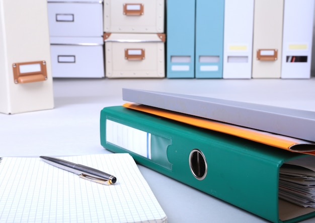 Folder file, note and pen on the desk.