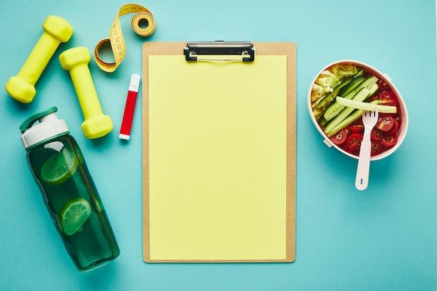 紙、水筒、ダンベル、巻尺、お弁当用のフォルダータブレットとヘルシーな野菜サラダ。運動計画と適切な栄養の概念