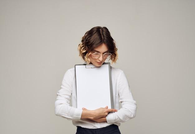 Папка с белым листом бумаги на сером в руках макет женщины.