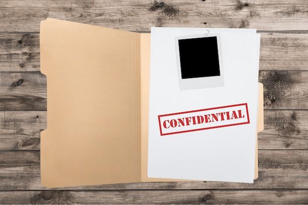 木製のテーブルに機密書類が入ったフォルダー