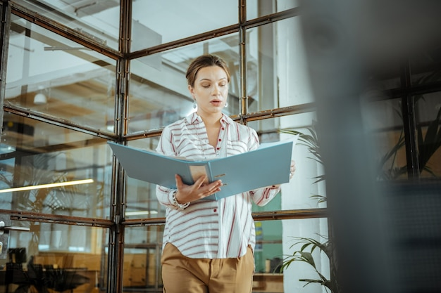 Папка с документами. темноволосая трудолюбивая беременная женщина держит папку с документами