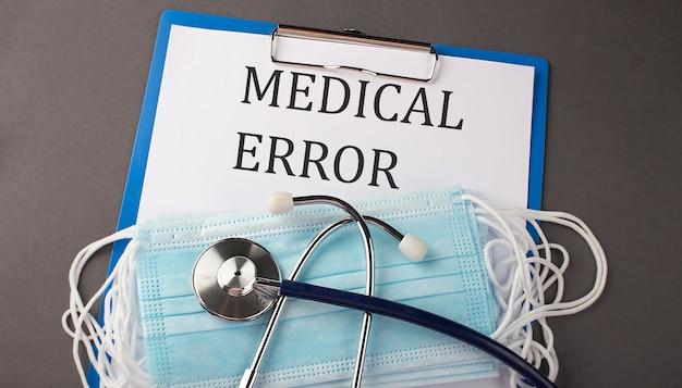 Папка с бумажным текстом медицинская ошибка на столе со стетоскопом и медицинскими масками