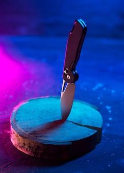 Folding beautiful knife, trendy colors neon smoky background