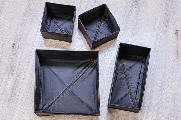 크기와 모양이 다른 검정색의 접이식 상자는 서랍을 별도로 보관할 수 있도록 설계되었습니다.