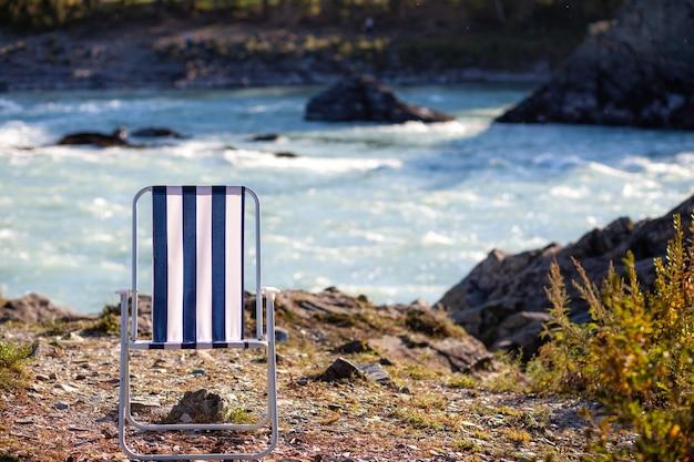 Складные стулья на берегу горной реки в погожий теплый день. спокойное и тихое место для отдыха и размышлений. снаряжение и туристический отдых.