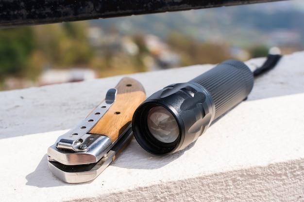 접는 칼과 손전등이 콘크리트 울타리에 놓여 있습니다. 관광 장비, 트레킹, 하이킹 및 캠핑 활동 개념. 재고 사진.