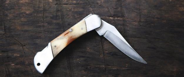 古い茶色のボード上の折りたたみナイフ