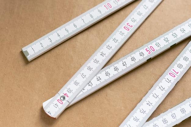 갈색 배경에 접는 눈금자 측정 도구입니다. 크라프트지 배경