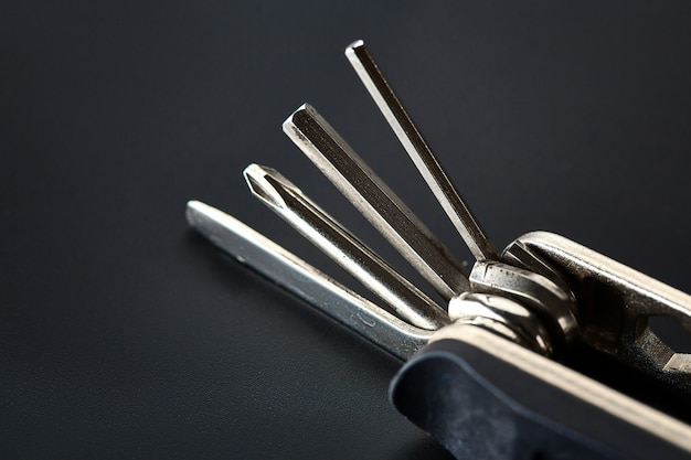 Folding screwdriver with different bits, closeup. professional instrument, worker equipment, screwing tools