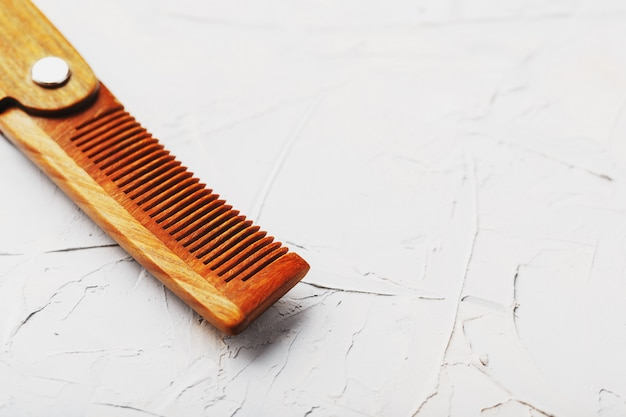Folding wooden comb on a gray wall.