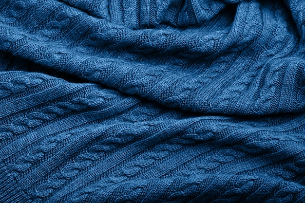 Folds of a knitted woolen blanket, blue color, top view background