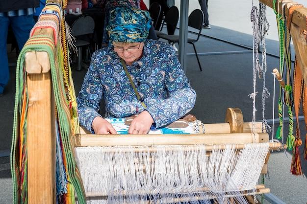민속 예술 축제. 여자는 손 베틀에 손으로 짜여져 있습니다. 직물은 수제입니다.