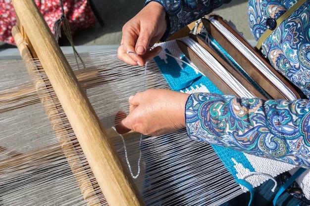 민속 예술 축제. 여자는 손으로 베틀에 직물을 만듭니다.