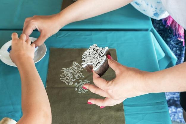 민속 예술제 예술가는 아이들에게 진부한 표현을 사용하여 천에 패턴을 그리는 법을 가르칩니다.