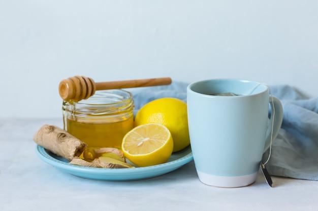 감기 치료를위한 민간 요법. 가벼운 테이블에 레몬 꿀, 레몬, 생강 및 차. 유기농 감기약. 감기에 대한 자연 요법