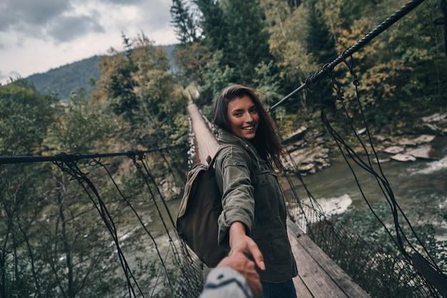 フォローしてください!吊橋を歩きながら彼氏と手をつないで美しい若い笑顔の女性