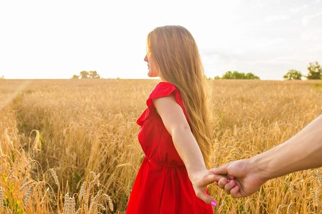 私についてきてください、美しい若い女性が麦畑で男の手を握っています