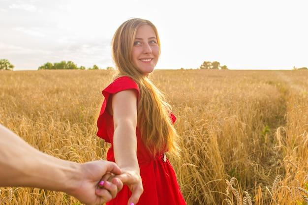 私に従ってください、美しい若い女性は麦畑で男の手を握っています。